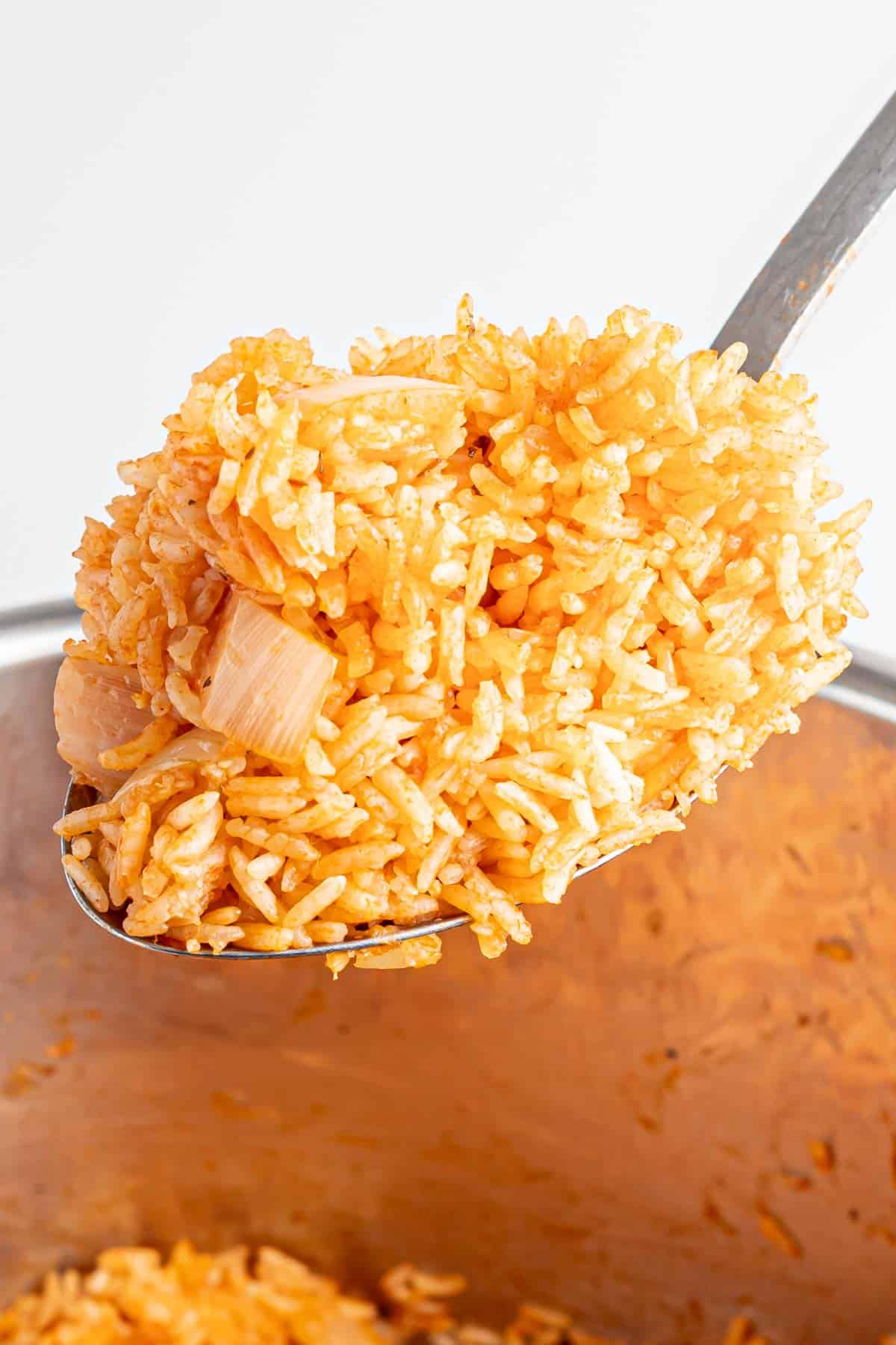 serving spoon picking up a scoop of cooked spanish rice out of the instant pot