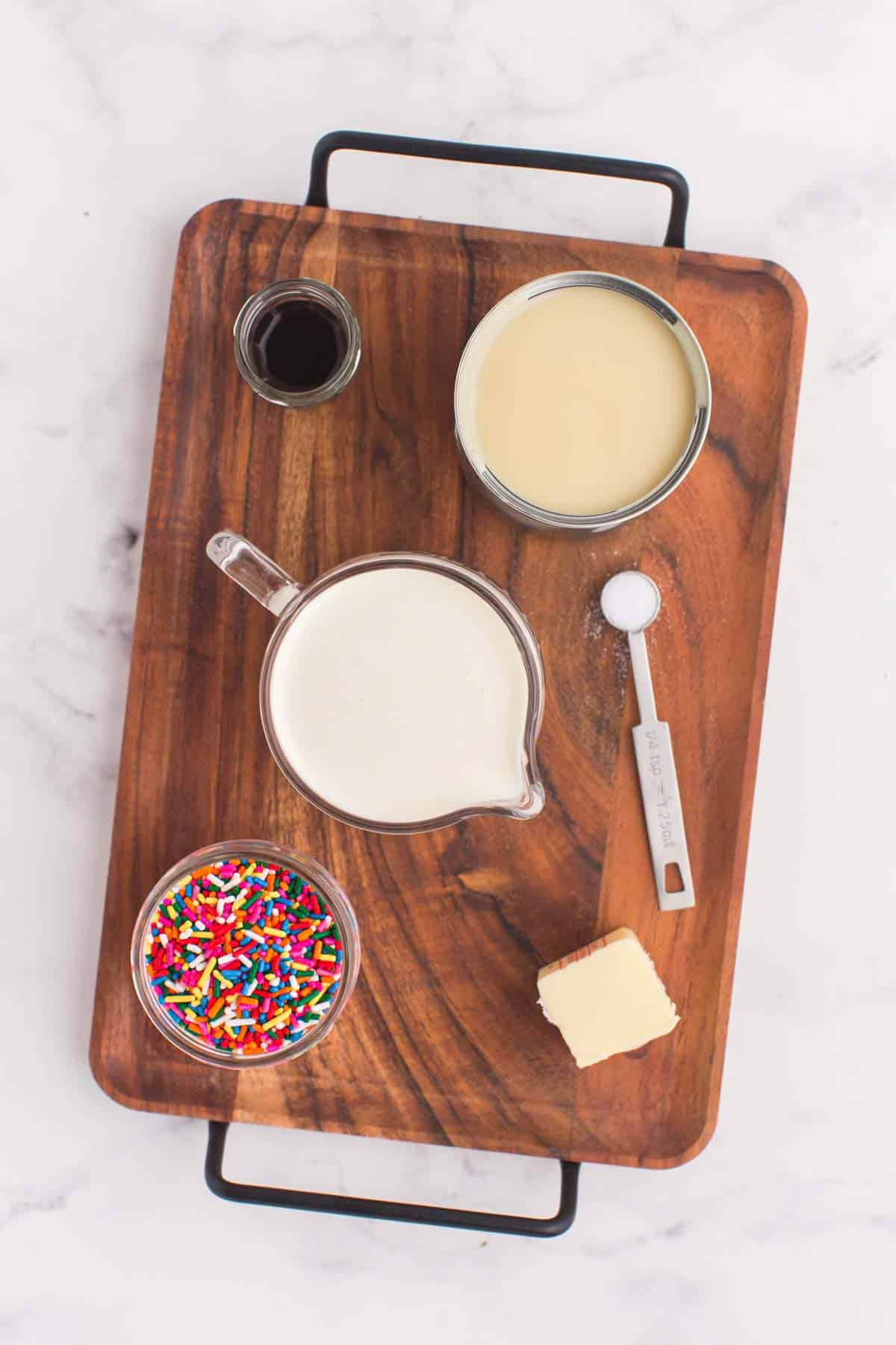 measuring cup of heavy cream, can of sweetened condensed milk, jar of vanilla extract, cube of butter, and a bowl of rainbow sprinkles on a wooden platter
