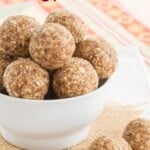 pineapple coconut energy balls in a white bowl with two on a napkin