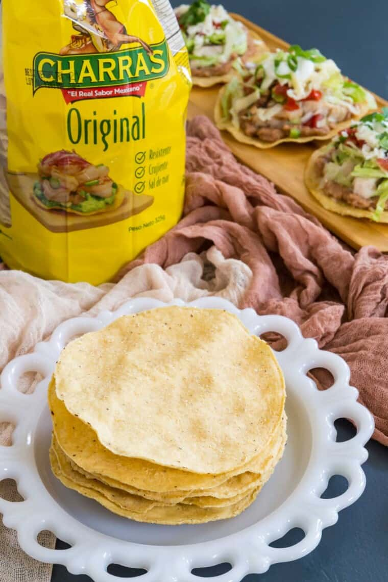a package of tostada shells with more on a plate and a platter of chicken tostadas in the background