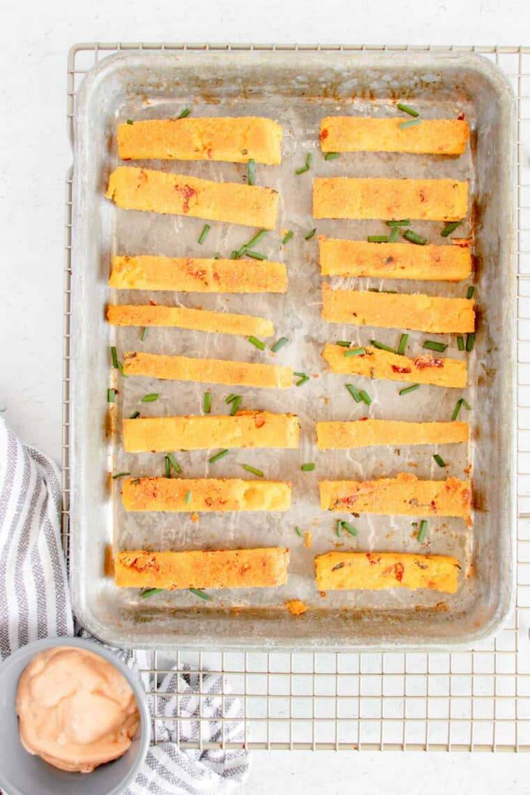 a baking sheet with polenta fries on a cooling rack with a small bowl of aioli