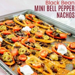 a sheet pan with baked bell pepper nachos with black beans, tomatoes, jalapeno slices, melted cheese, and dollops of sour cream on several