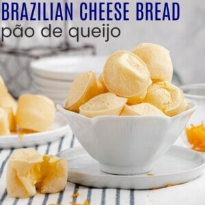 a white bowl filled with brazilian cheese bread and one of the cheesy bites split open to see the middle