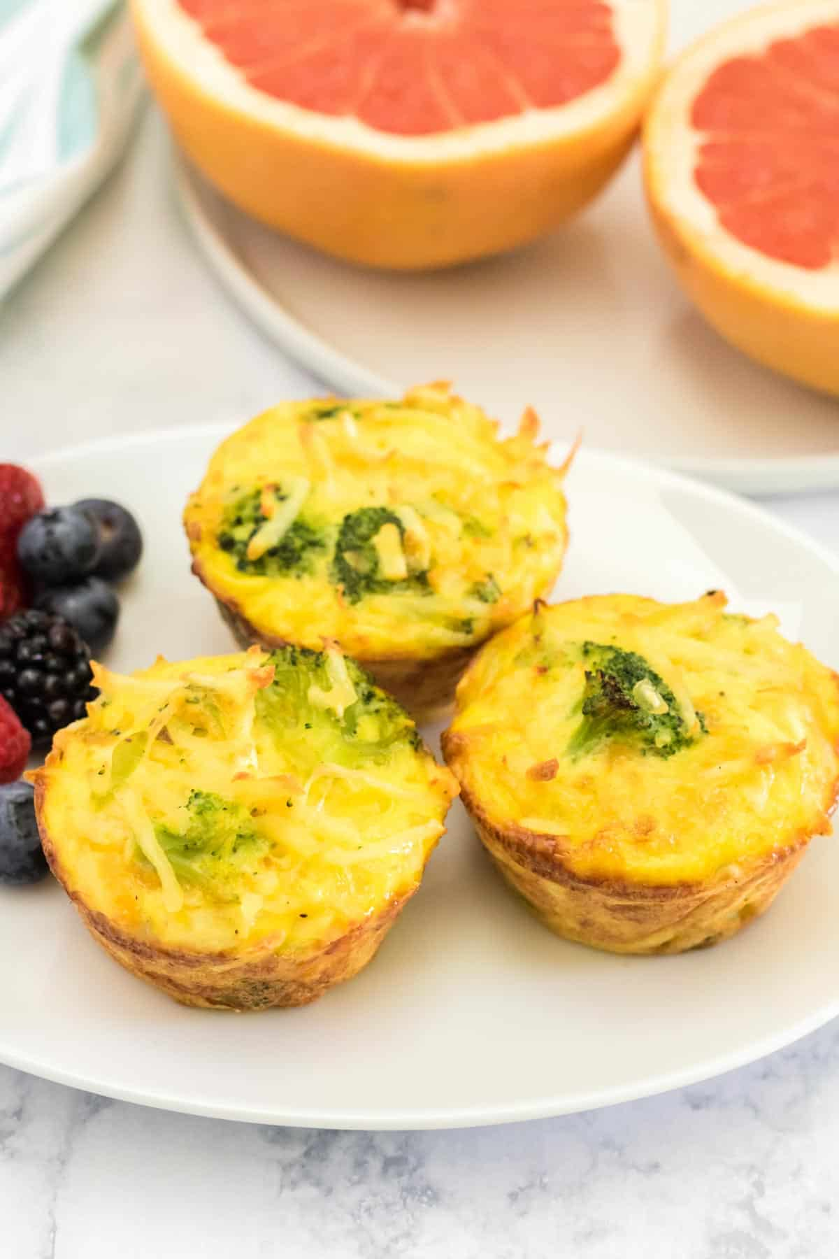 three broccoli cheese egg muffins on a plate next to a small plate with a grapefruit cut in half