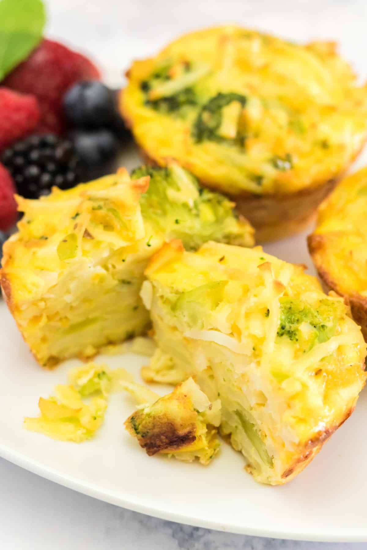 broccoli potato cheese egg muffin cut in half on a white plate