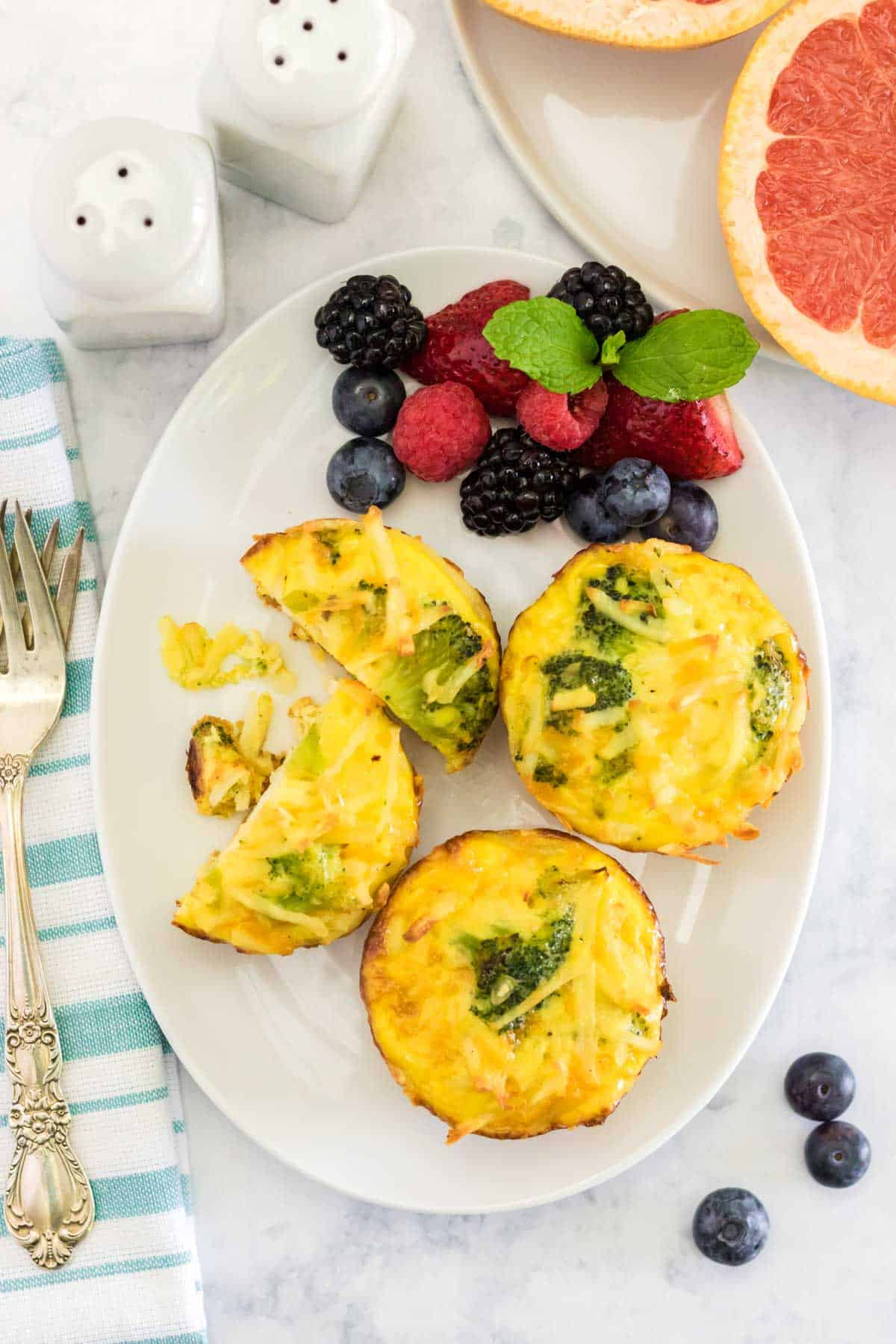 three egg muffins on a white oval plate with one cut in half and served with berries