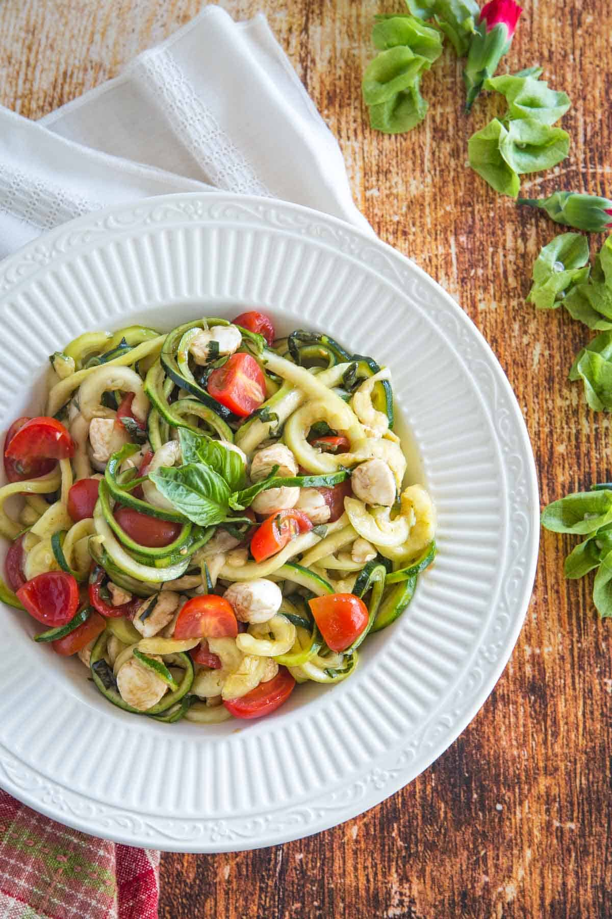 zoodles caprese salad in a serving bowl on a wooden tabletop next to a red plaid napkin