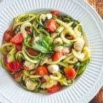 a serving bowl of zoodles with tomatoes, fresh mozzarella, and basil on a wooden table