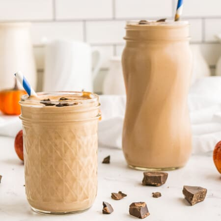 Two pumpkin chocolate smoothies on a counter in front of a white tile wall with white ceramic pitchers of various sizes against the wall