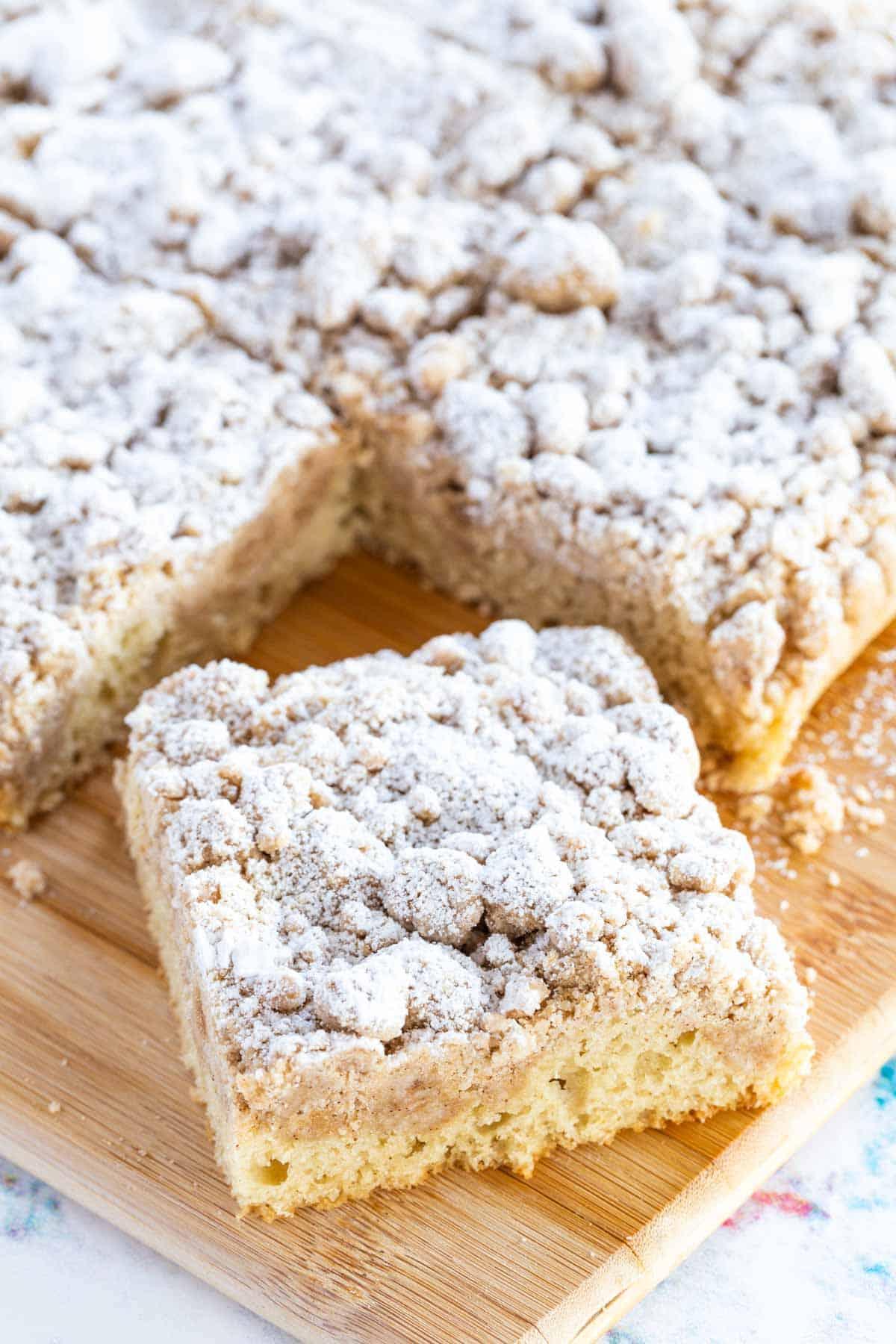 slice of gluten-free crumb cake on a wooden board