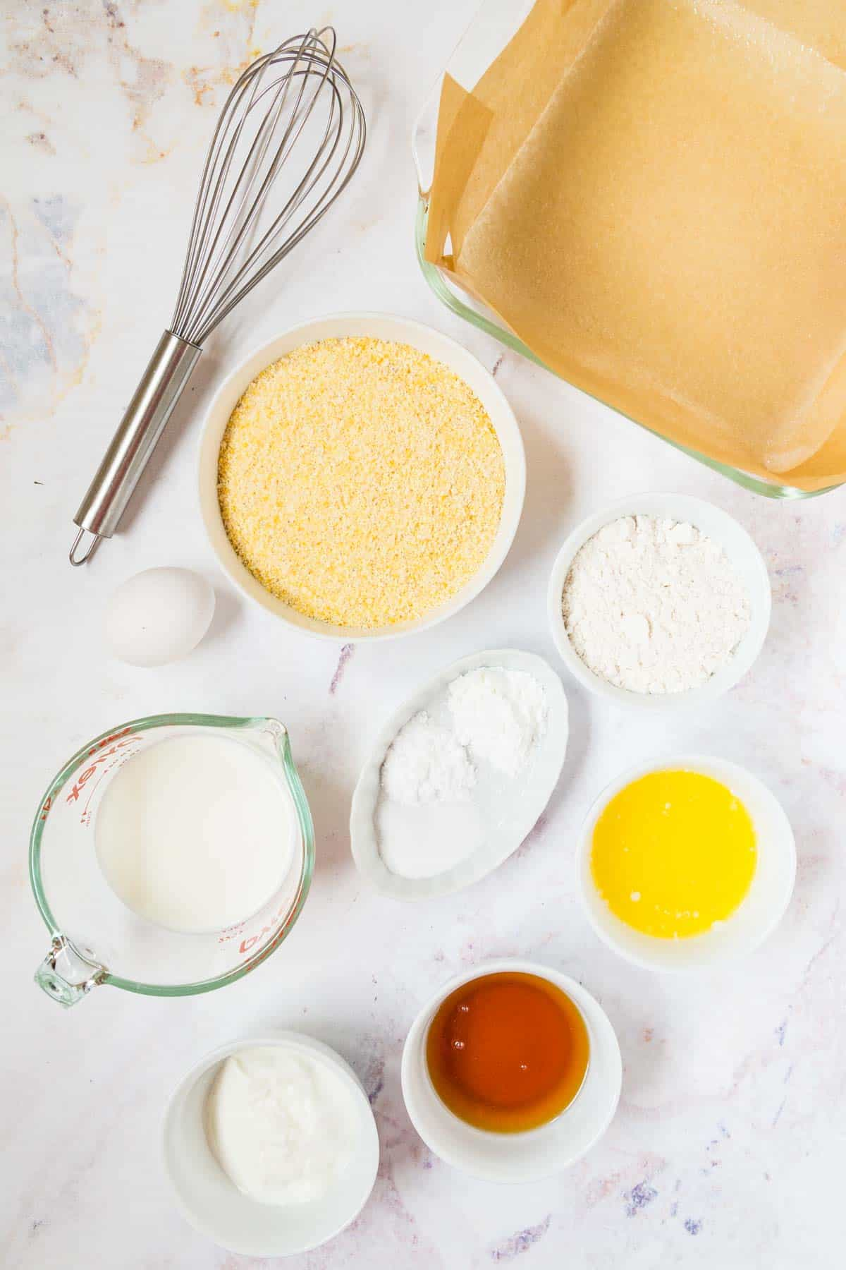 ingredients in small bowls with cornmeal, flour, honey, yogurt, and milk