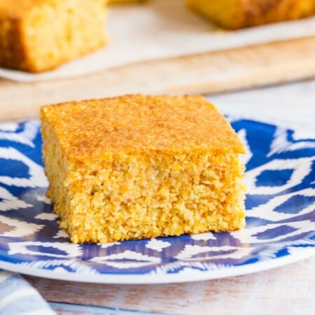 a piece of gluten free cornbread on a blue and white plate