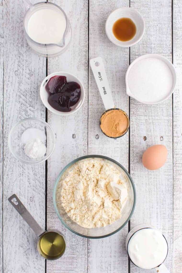 bowls of gluten free flour, salt, baking powder, sugar and vanilla extract, a pitcher of milk, and measuring cups with peanut butter, yogurt, and oil