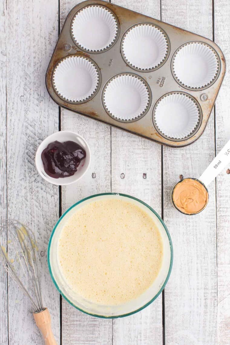 vanilla cupcake batter in a bowl with a whisk, a cupcake pan with liners, a measuring cup of peanut butter, and a small bowl of jelly