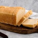 sliced loaf of sandwich bread on a wooden cutting board