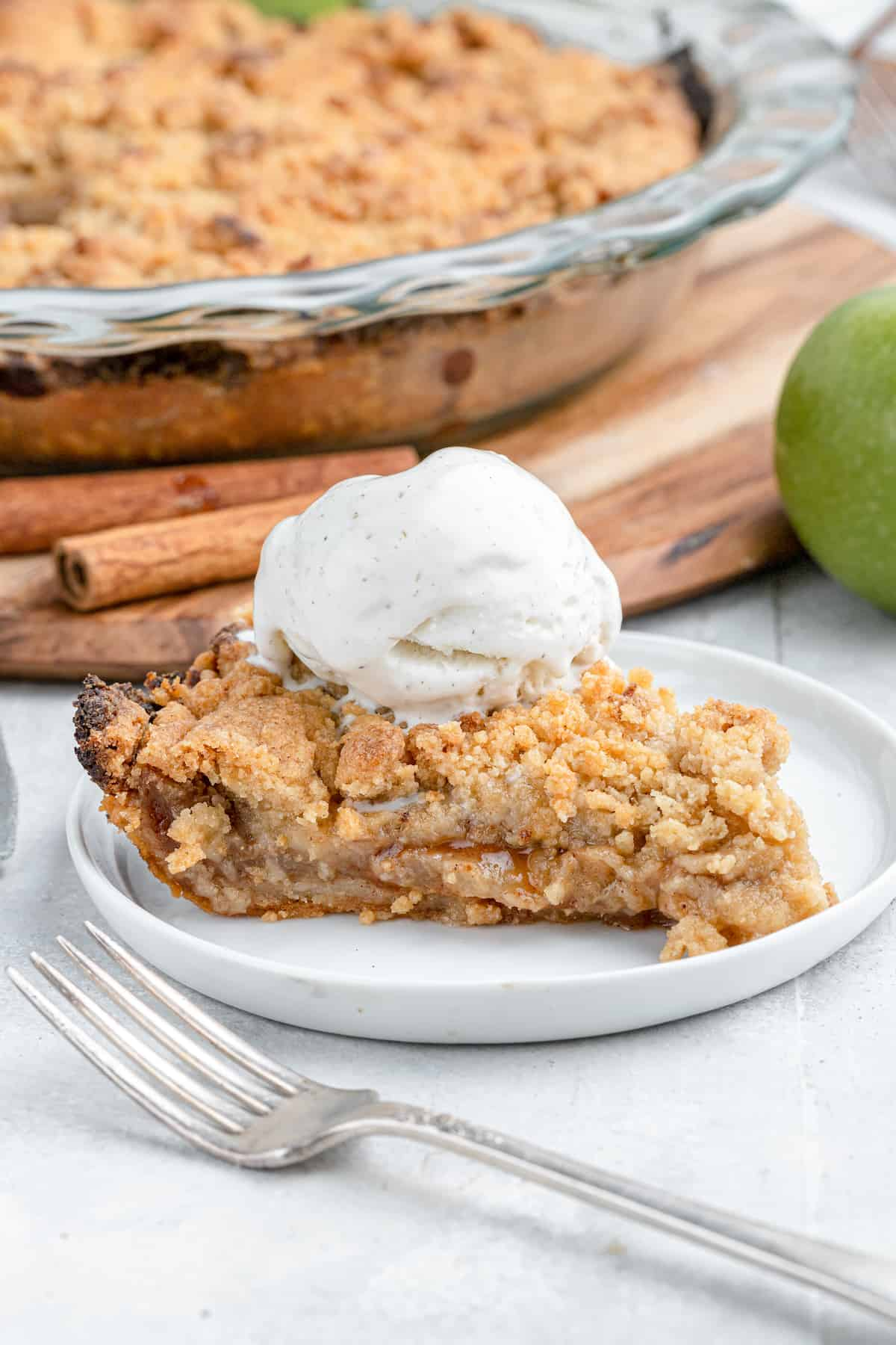 close up on a slice of dutch apple pie with ice cream and cinnamon sticks