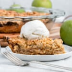 slice of dutch apple pie topped with a scoop of ice cream next to a granny smith apple and the rest of the pie in a glass pie plate