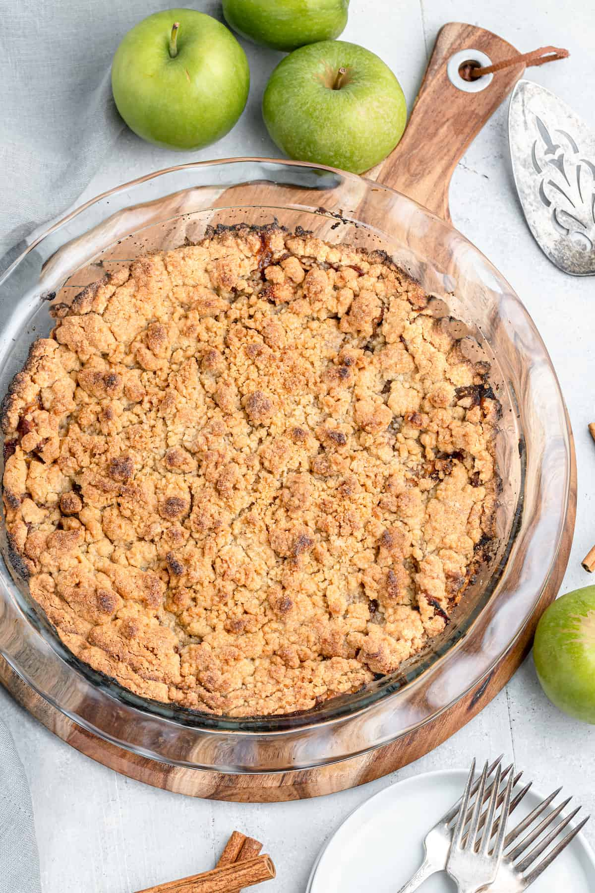 whole apple pie with crumb topping with raw granny smith apples on the side