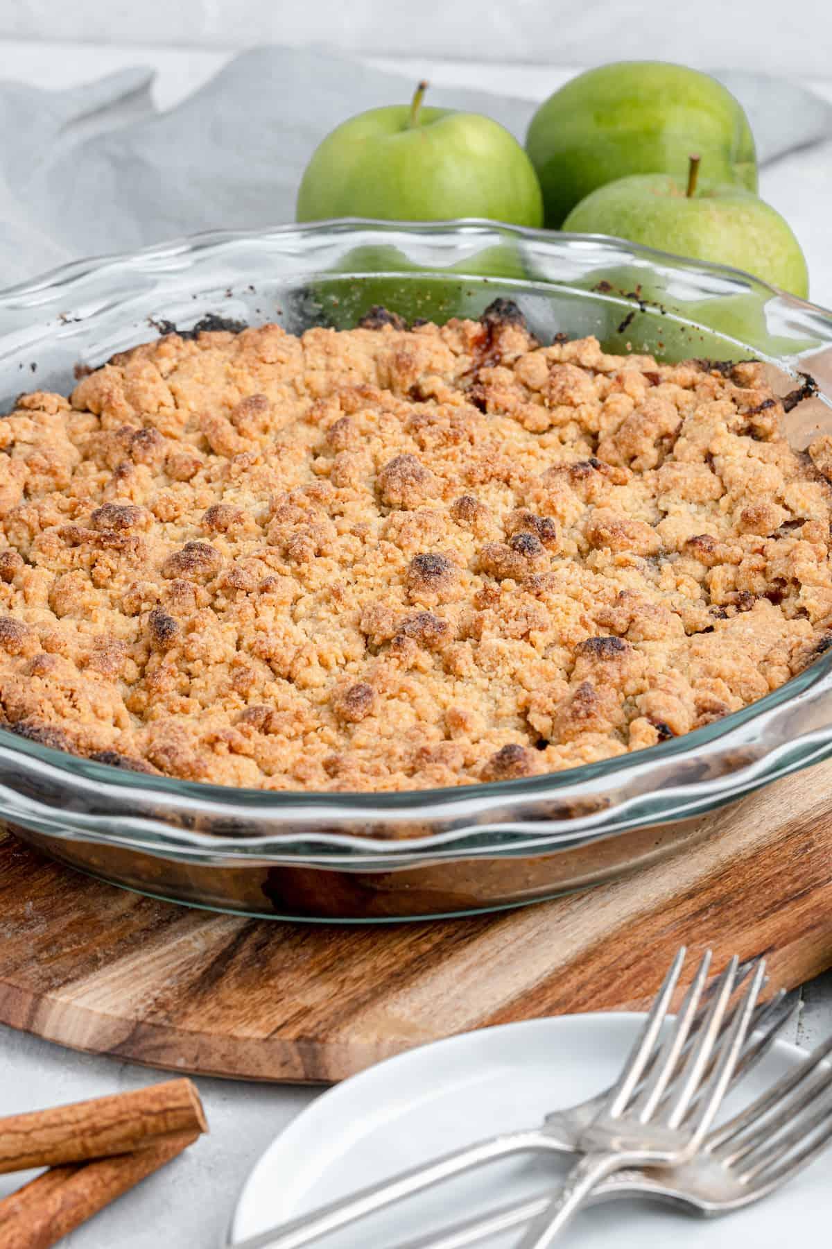golden baked dutch apple pie in a glass pie plate