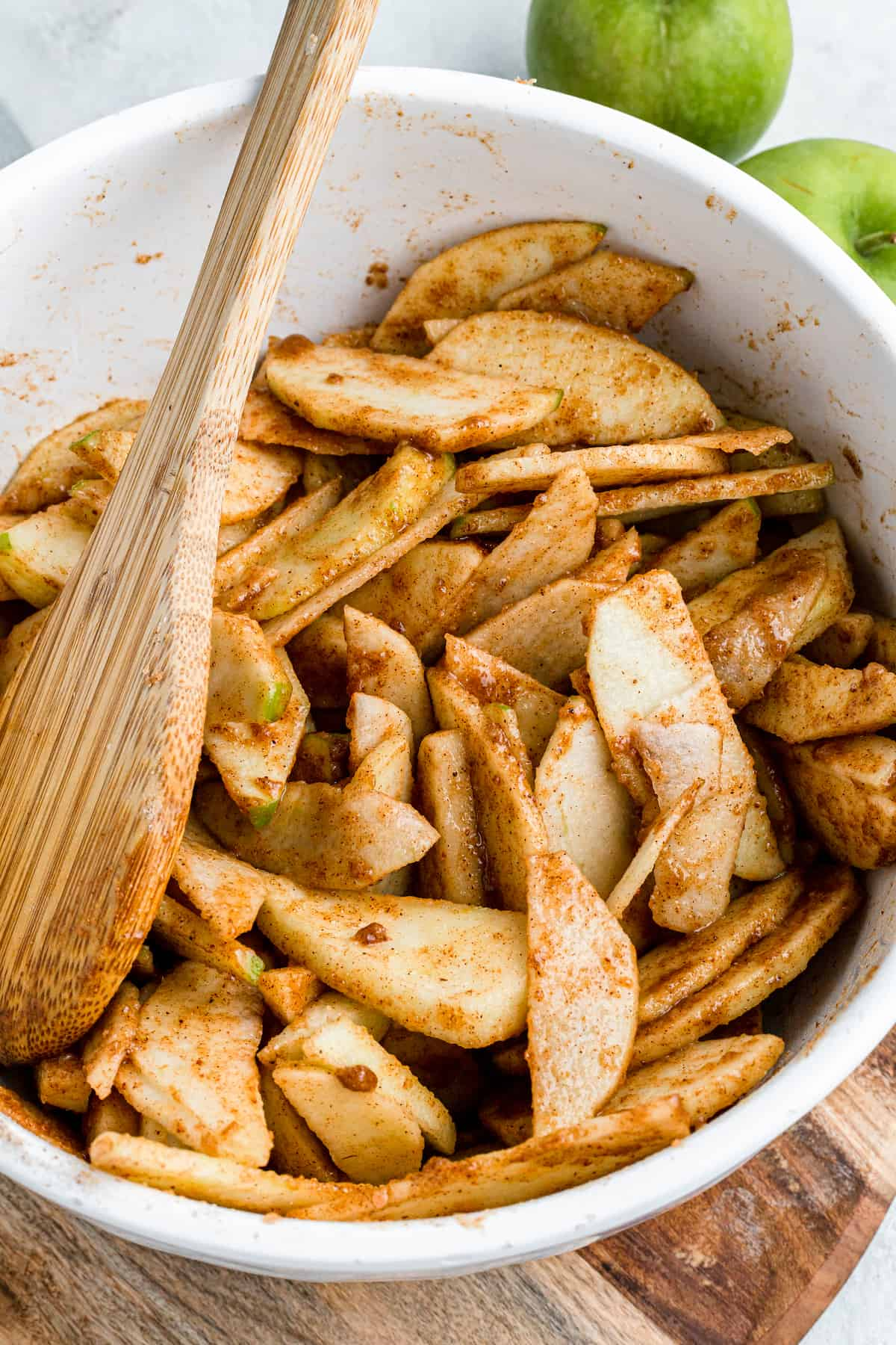 slices of apples in cinnamon sugar in a mixing bowl
