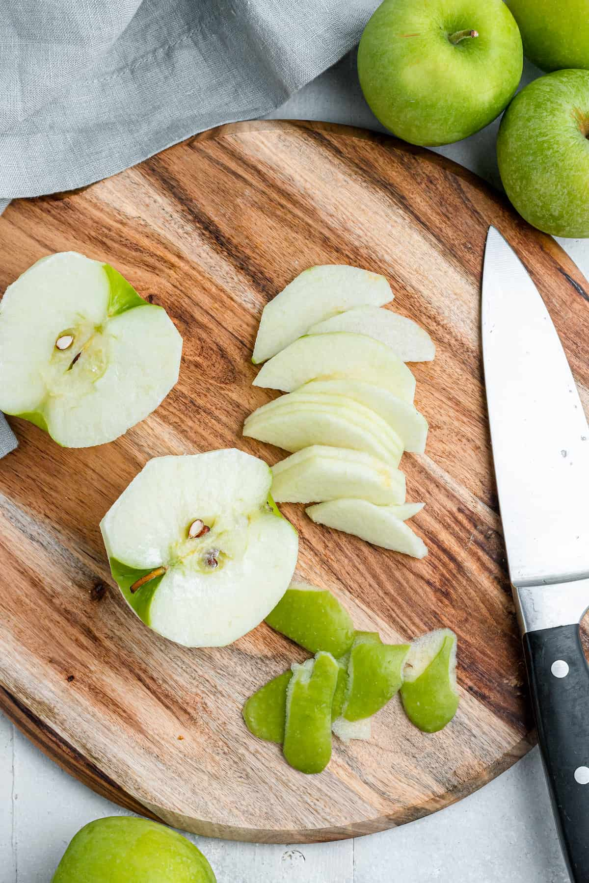 slicing green apples on a wooden cutting board