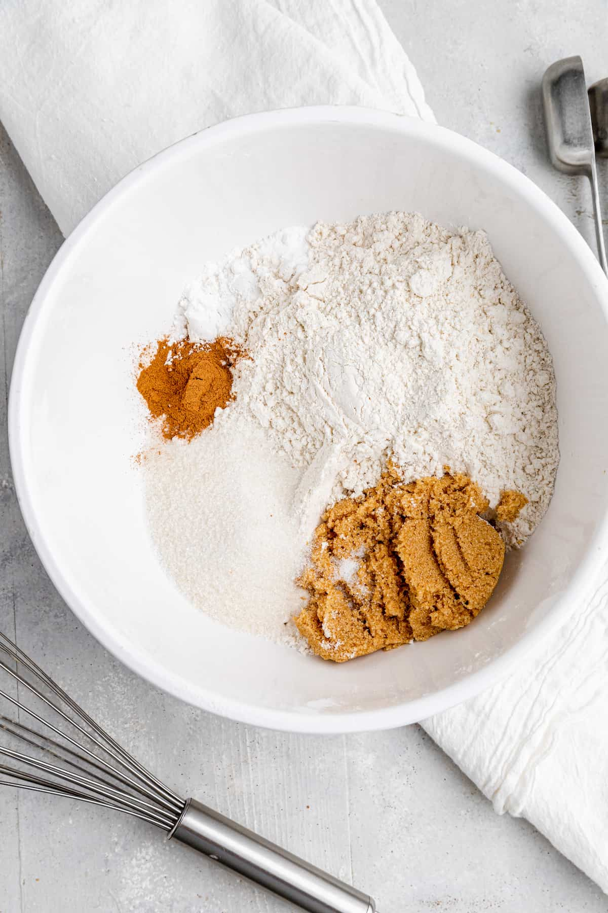 dry ingredients flour, cinnamon, baking powder and salt in a white mixing bowl