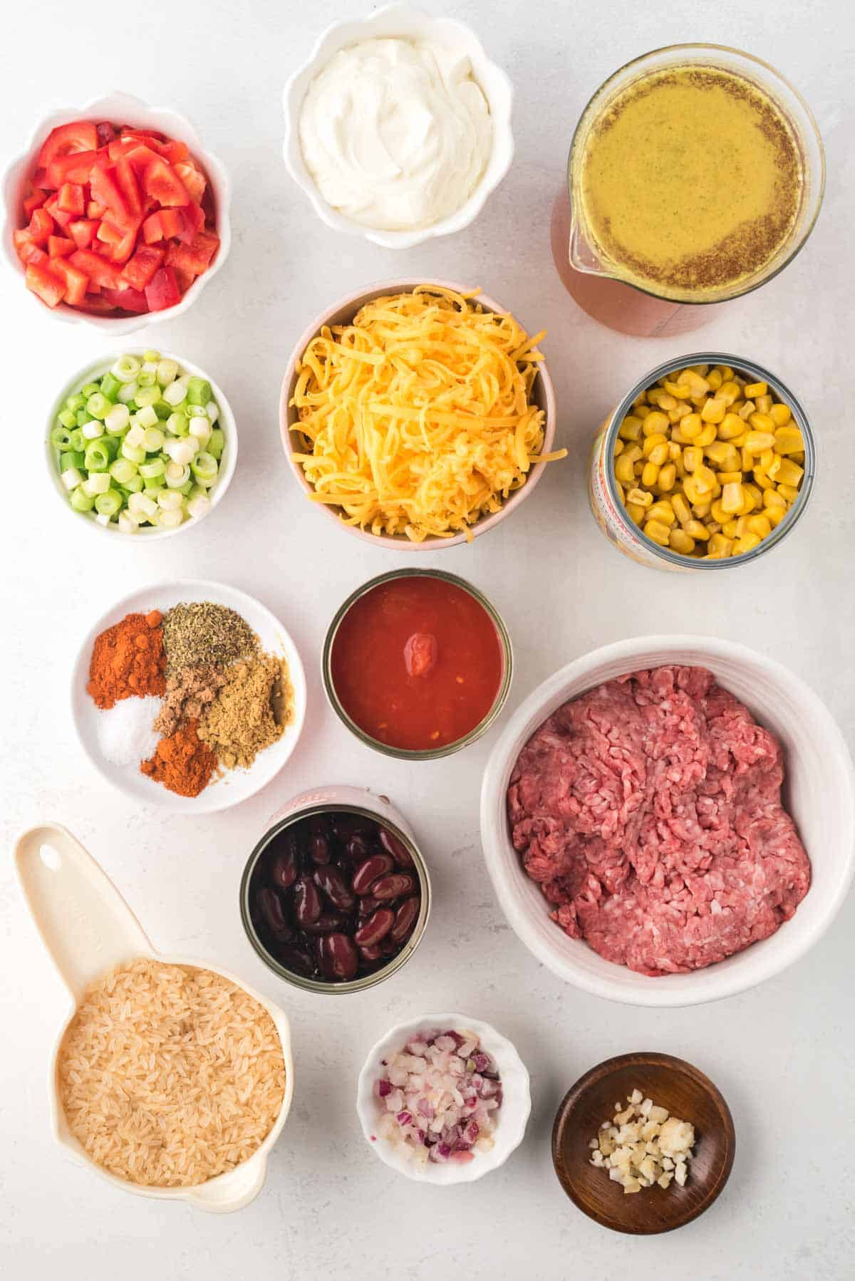 bowls of raw ground beef, garlic, onion, uncooked rice, various spices, sliced green onions, shredded cheesechopped red bell pepper, sour cream, beef broth, and cand of kidney beans, diced tomatoes, and corn on a tabletop