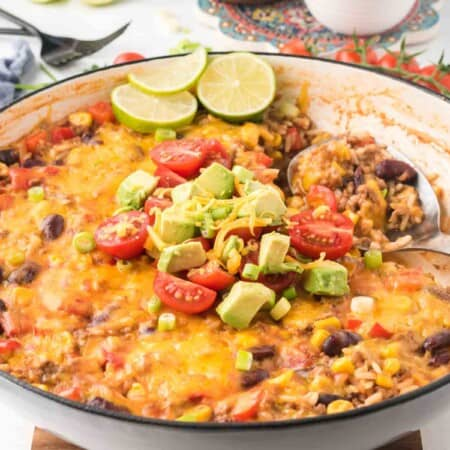 ground beef taco skillet in a pan with serving spoon and a pile of tomatoes, avocado, and scallions on top plus three lime slices