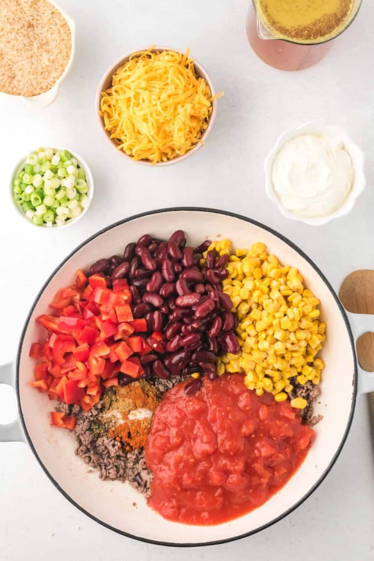 cooked ground beef in a skillet with the canned diced tomatoes, corn, kidney beans, chopped red bell pepper, and spices added on top
