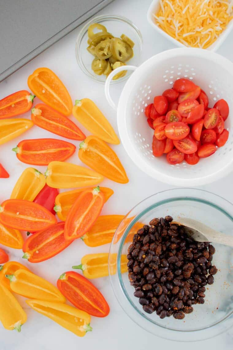 raw mini bell pepper sliced in half next to a bowl of black beans coated in taco seasoning, a colander of grape tomatoes, and bowl of jalapeno slices and shredded cheese