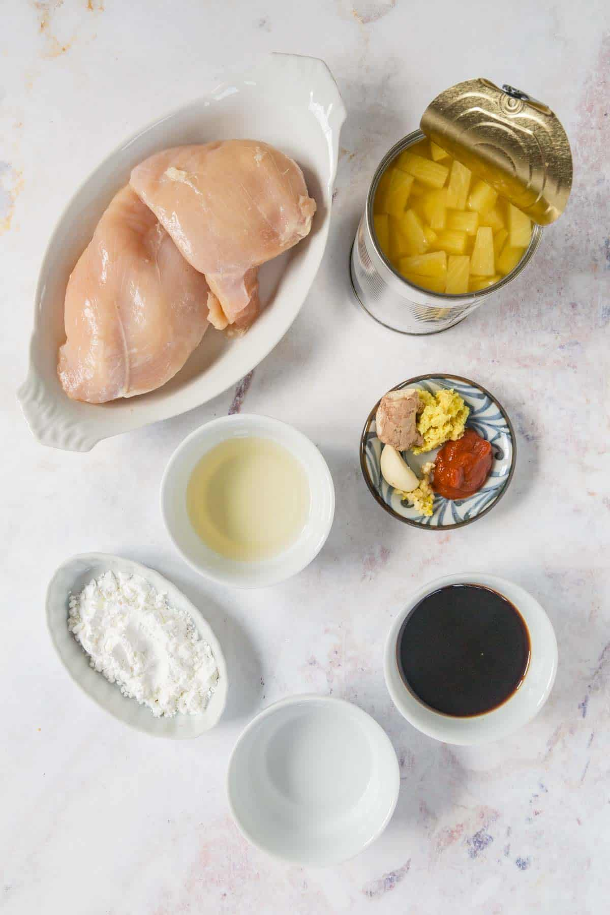 raw chicken breast in a dish, plus bowls of soy sauce, rice vinegar, cornstarch, water, garlic, ginger, and sririacha, and acan of pineapple tidbits on a marble tabletop