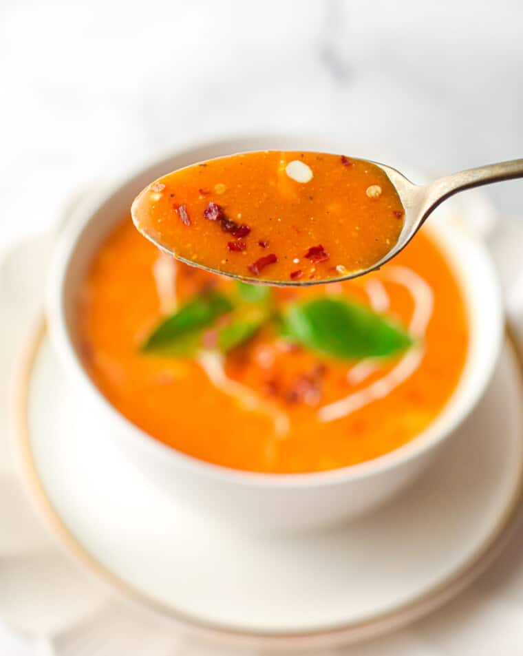 a soup spoon with tomato soup held above a bowl