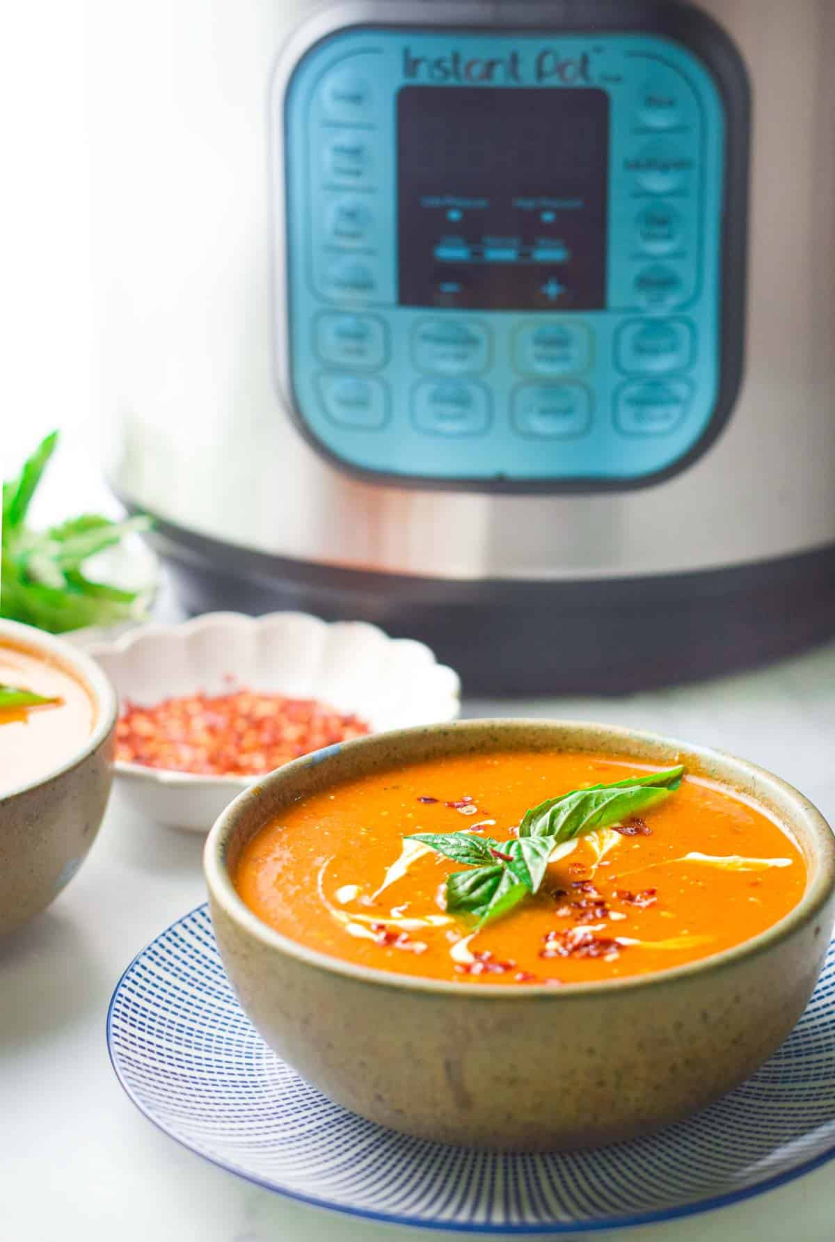 a bowl of tomato basil soup garnished with a drizzle of cream and a small bowl of chili flakes next to an instant pot