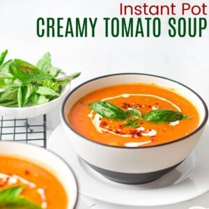 black and white bowl filled with creamy tomato soup with a drizzle of cream, and basil leaves and red pepper flakes floating on top
