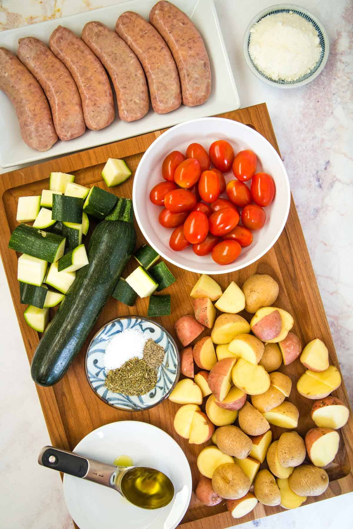 uncooked turkey sausage on a plate next to a cutting board with chopped potatoes and zucchini, bowl of grape tomatoes, parmesan cheese, and seasonings, and a spoon of olive oil