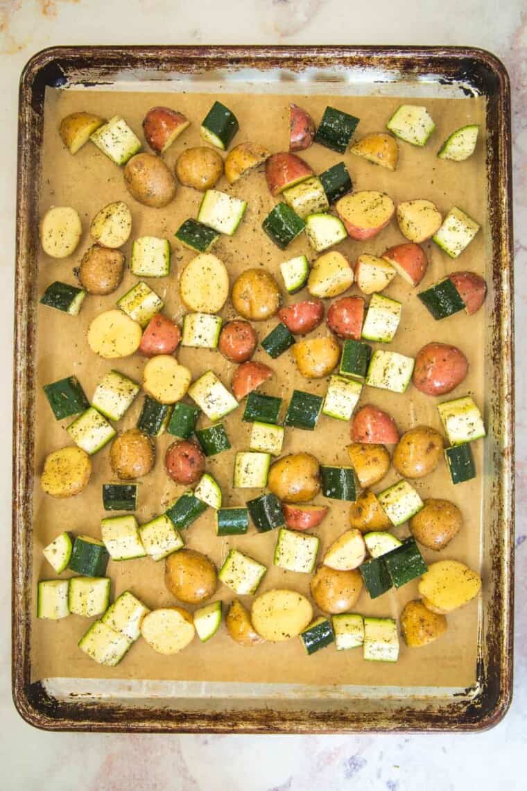 chunks of potatoes and zucchini coated with olive oil and herbs spread out on a baking sheet
