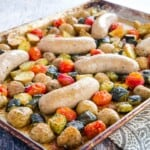 baking sheet with roasted turkey sausage, chunks of potatoes and zucchini, and grape tomatoes