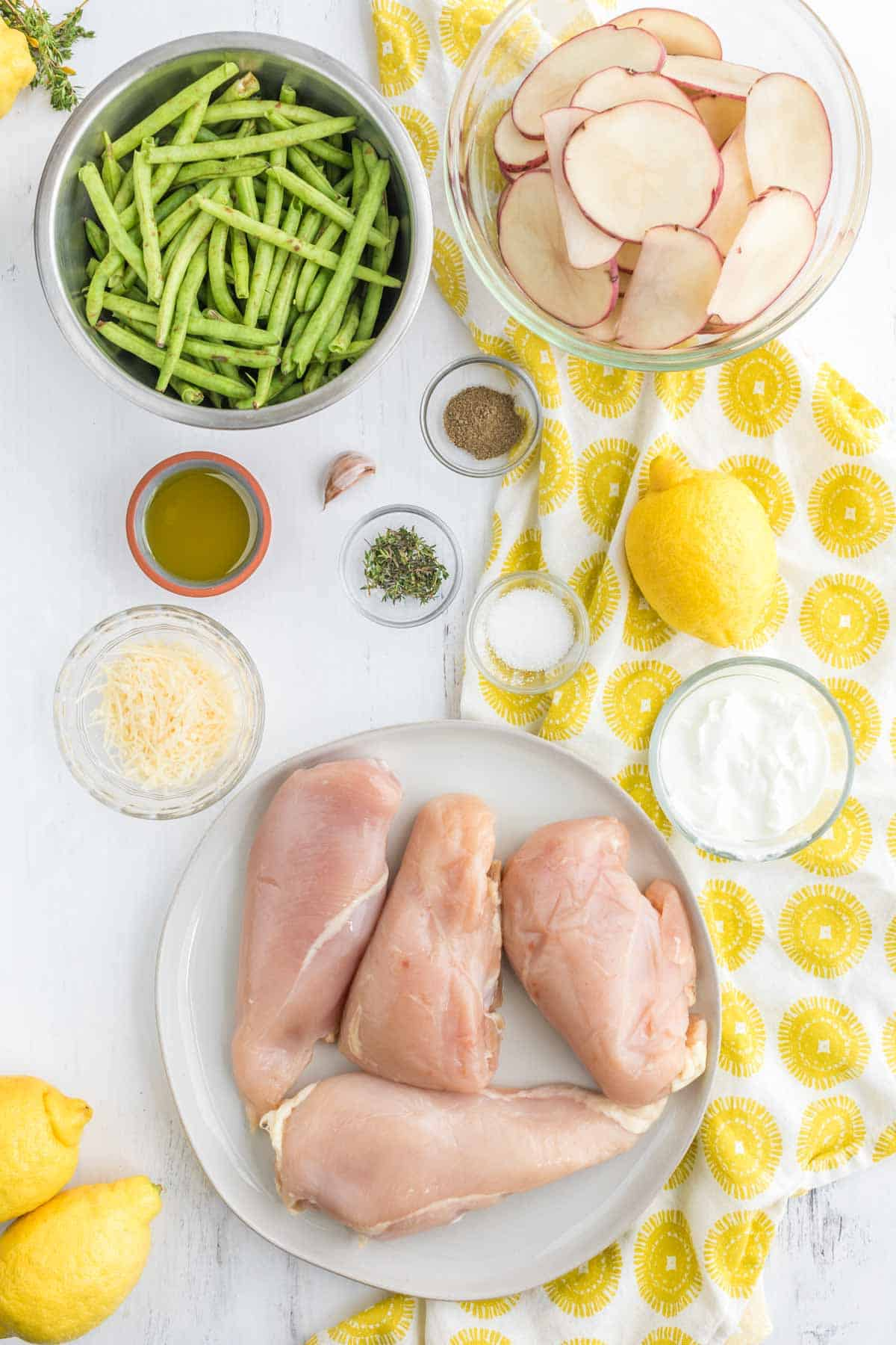four raw chicken breasts on a plate with bowls of sliced potatoes, green beans, Greek yogurt, olive oil, salt, pepper, parmesan cheese, fresh thyme, a garlic clove and a lemon