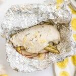 opened up lemon chicken foil packet after it has been cooked next to a yellow and white napkin with a fork and a knife