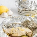 opened up lemon chicken foil packet with green beans and potatoes on a plate