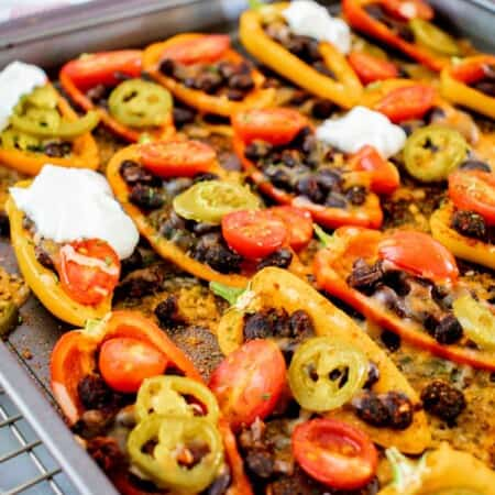 black bean bell pepper nachos with melted cheese on a sheet pan sitting on a cooling rack