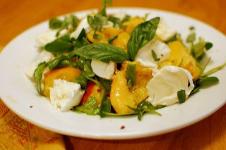 A Peach Salad on a Plate on Top of a Wooden Dining Table