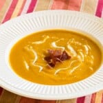 bowl of butternut squash soup garnished with crispy prosciutto next to a spoon and a cloth napkin on a striped placemat