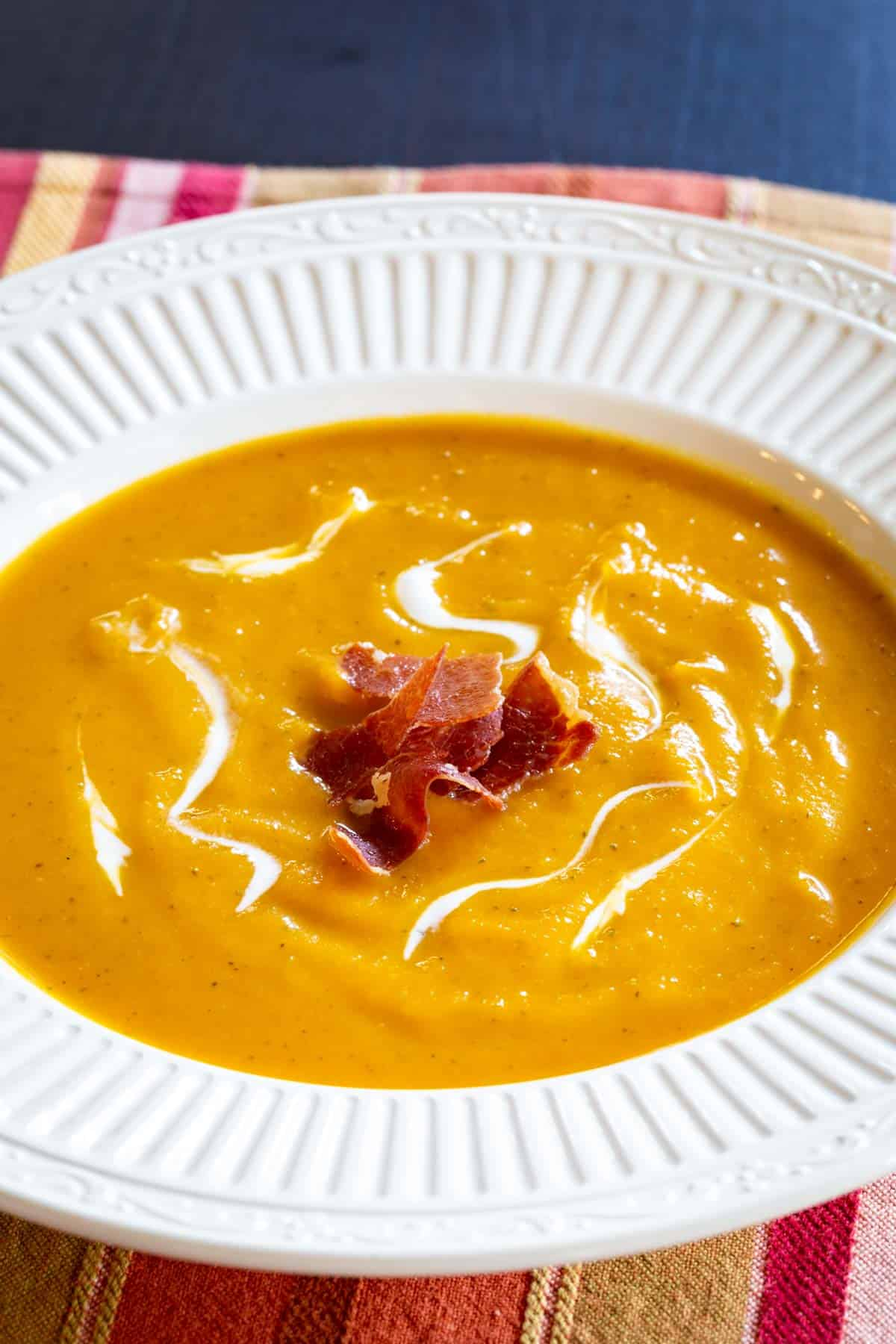 butternut squash soup in a white bowl with a scalloped edge on top of a striped placemat