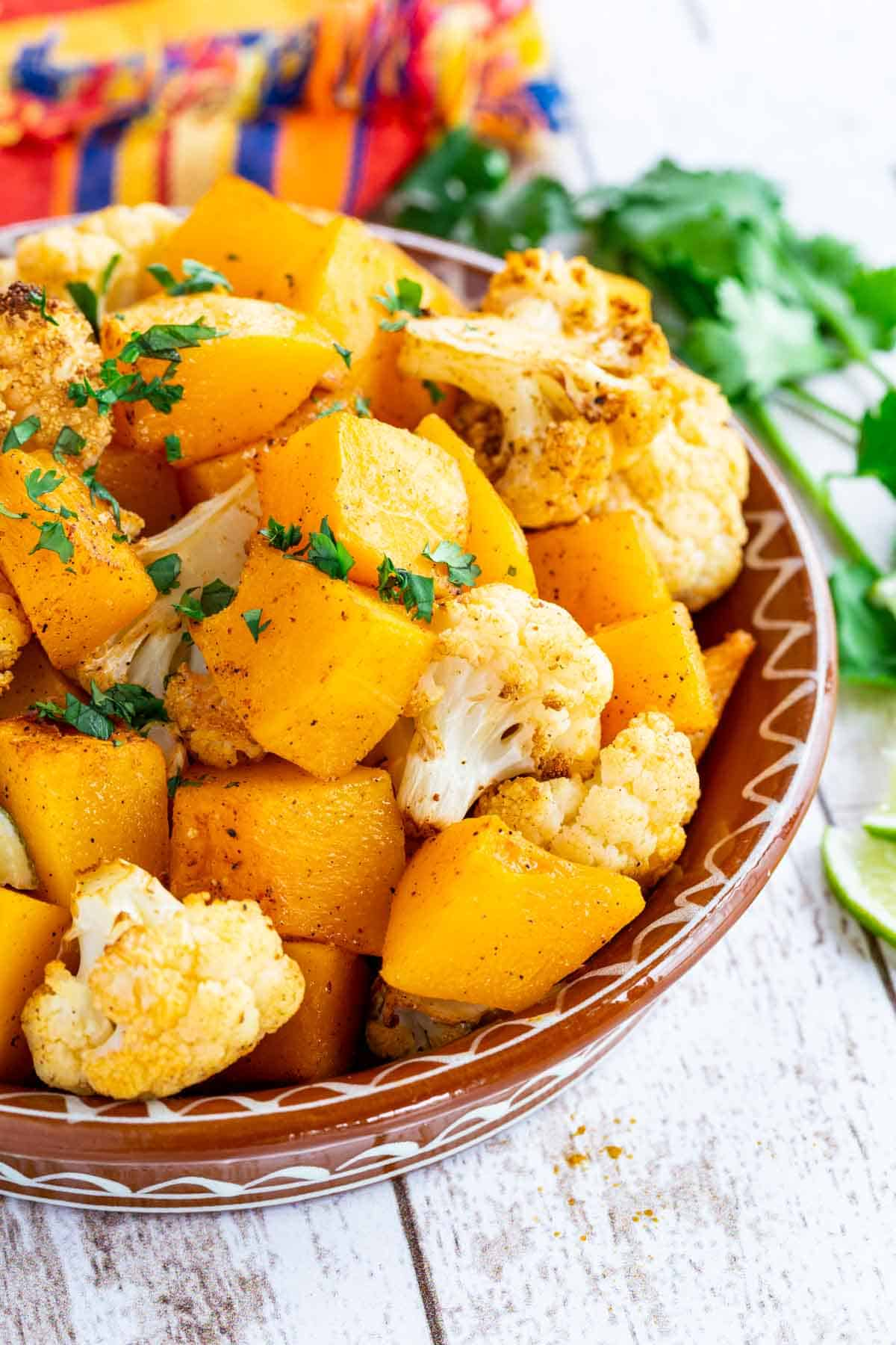 a dish of roasted cauliflower and butternut squash on a colorful striped napkin next to a sprig of cilantro