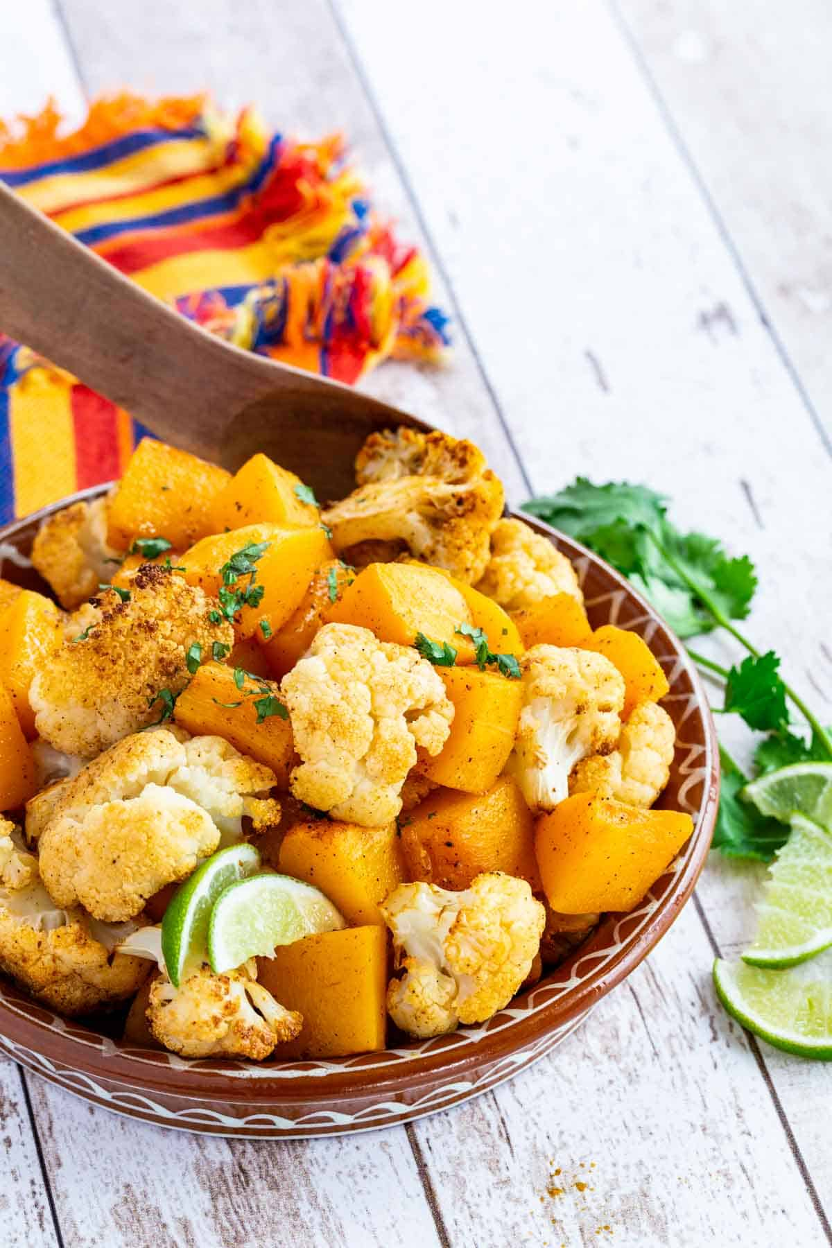 wooden spoon resting in a clad dish of roasted butternut squash and cauliflower florets garnished with lime wedges and cilantro