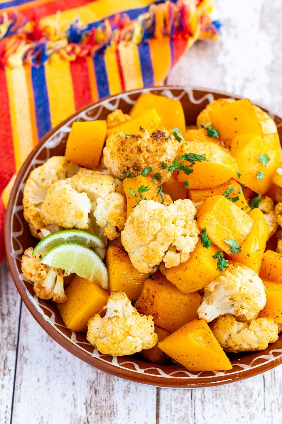 spicy roasted cauliflower and butternut squash garnished with lime slices and minced cilantro in a clay dish on top of a colorful striped cloth napkin
