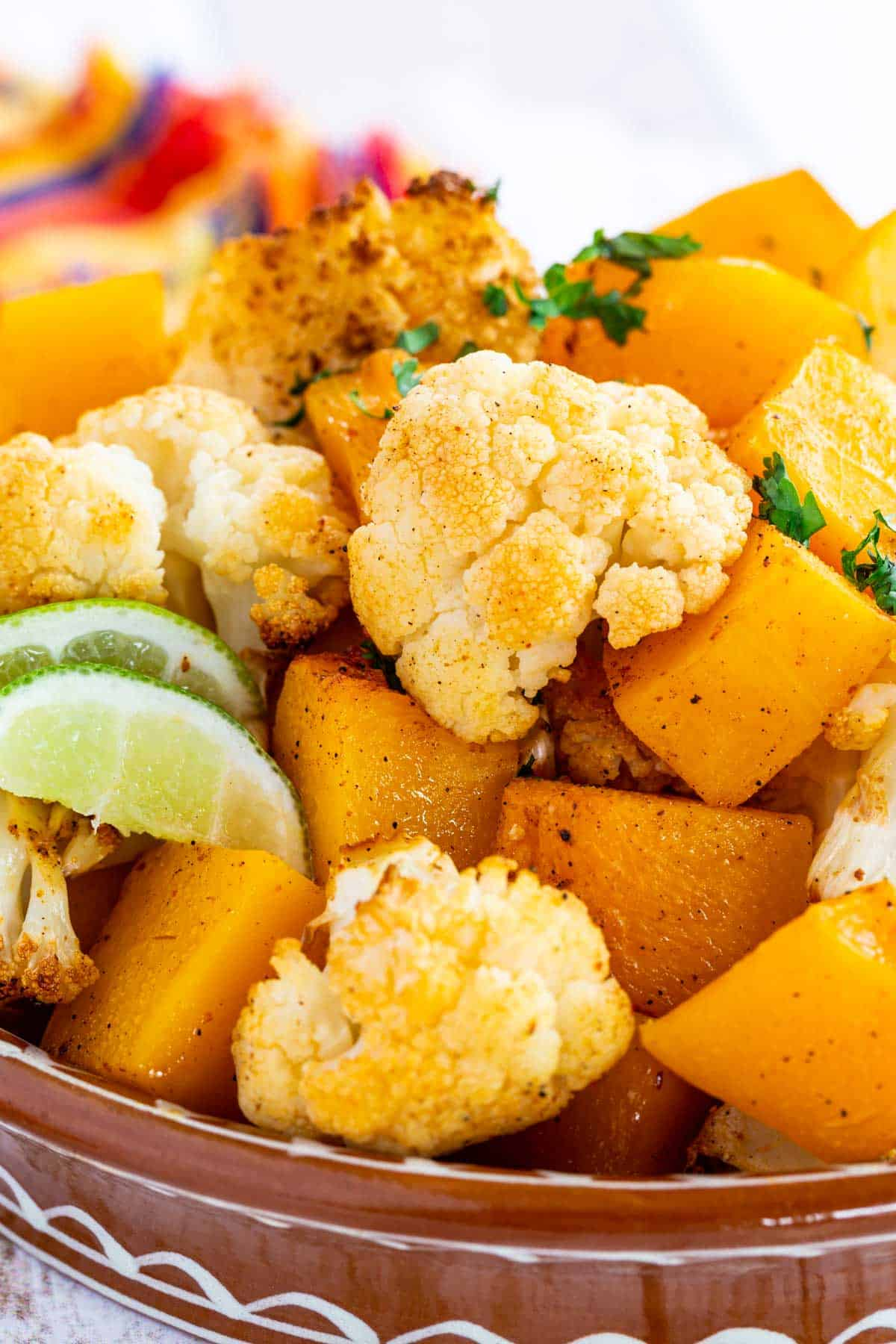 closeup of the roasted butternut squash cubes and cauliflower florets with a couple of lime wedges in the bowl too