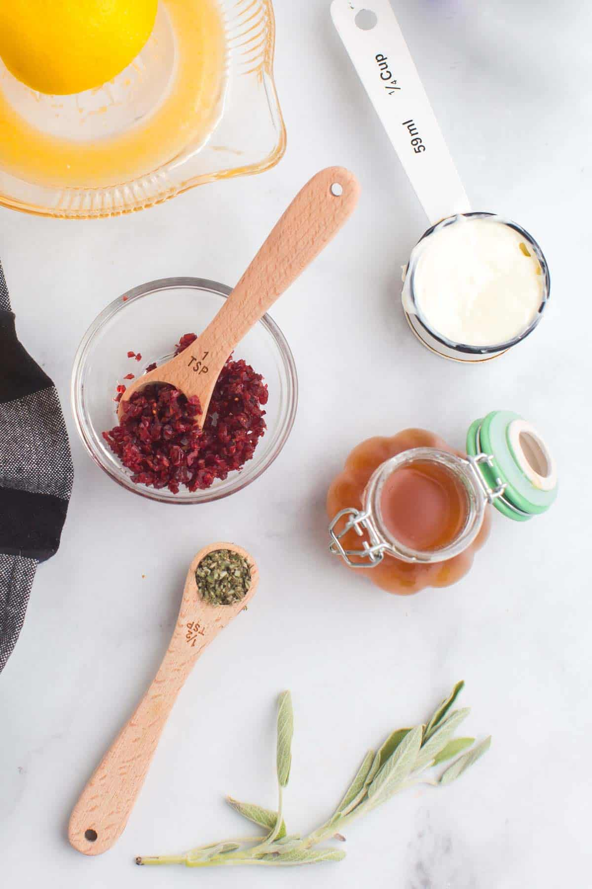 an orange being squeezed on a juicer, a bowl of chopped dried cranberries, a sprig of sage with some minced in a measuring spoon, a bottle of honey, and butter in a measuring cup