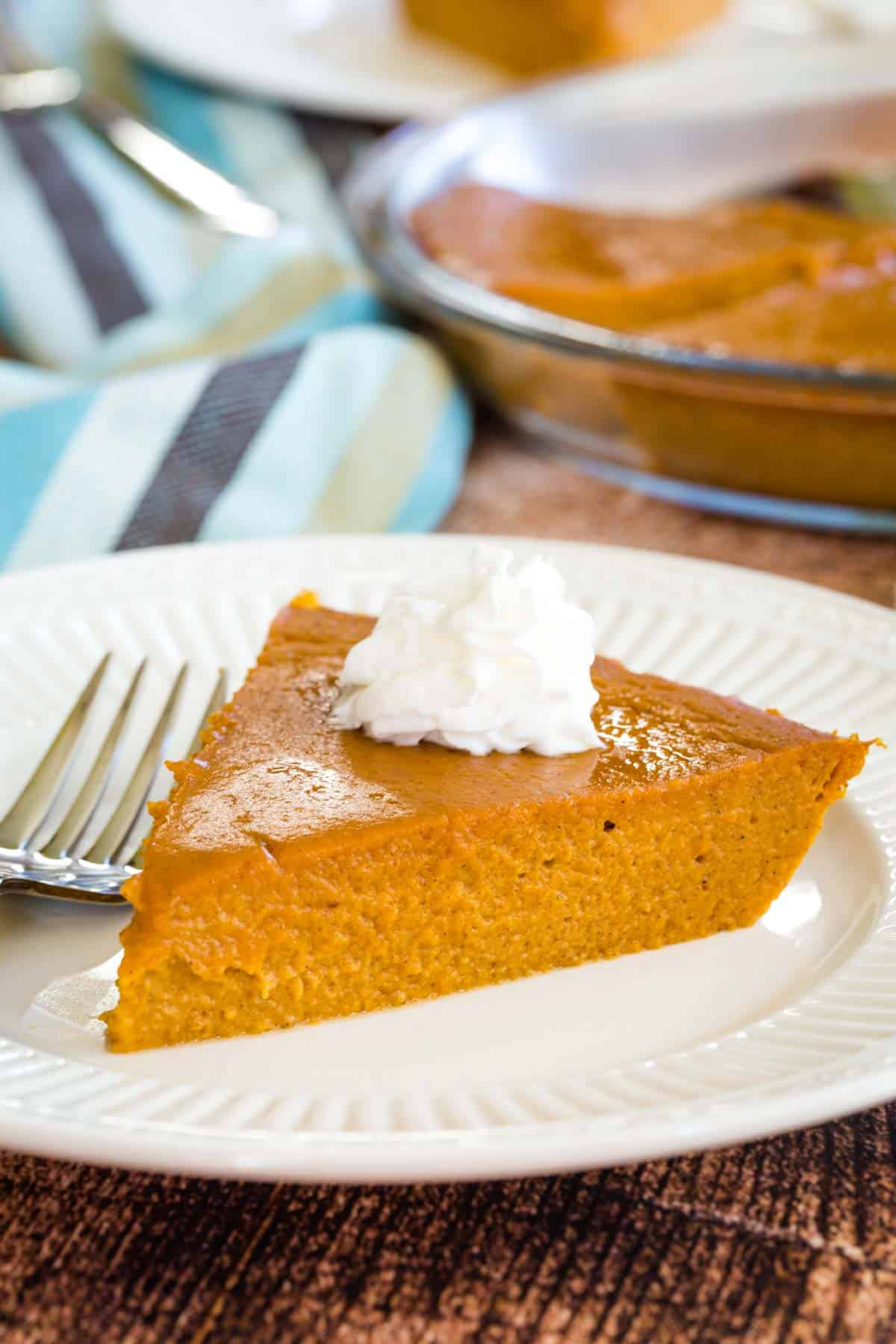 a slice of crustless pumpkin pie on a plate topped with a bit of whipped cream